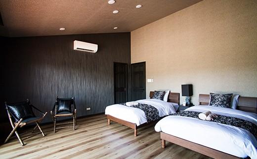 黒い壁に個性的なチェアの存在感、モノクロームを基調としたモダンなベッドルーム。