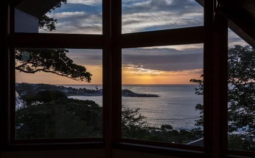大海原の夕景を大きな三角窓から眺めながら