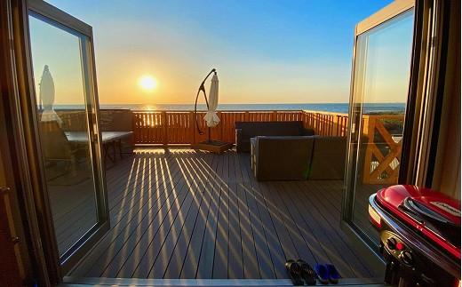 沈む太陽と美しい夕焼けを背景にしたダイニングテラスでの夕食は特別!
