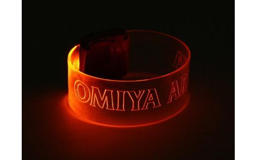 バングルはスイッチを押すと、クリアバンド部分に「OMIYA ARDIJA」のロゴがオレンジのライトで浮かび上がります。