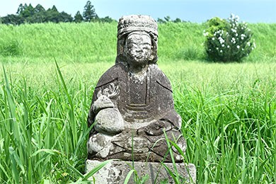 田んぼの近くにある石像「田の神さあ」