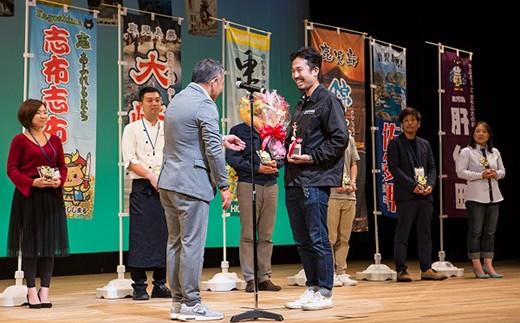生産者アワード 『グランプリ』を受賞し、審査員長からトロフィーを授与する出水田一生氏