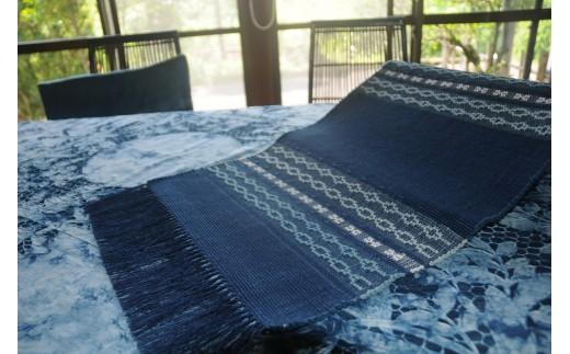 深みのある青と白の対比が心地よい手織りのテーブルセンター。天然灰汁発酵建て藍染めの技法を用い、花織を組み合わせた1枚。