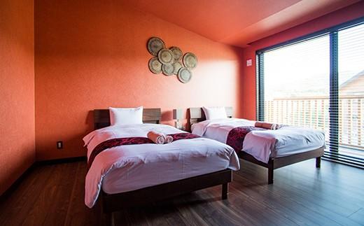 ブラッディオレンジを絞ったようなトロピカルなカラーが印象的なベッドルーム。