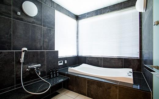 ダークカラーの石に包まれた開放感のあるバスルーム。