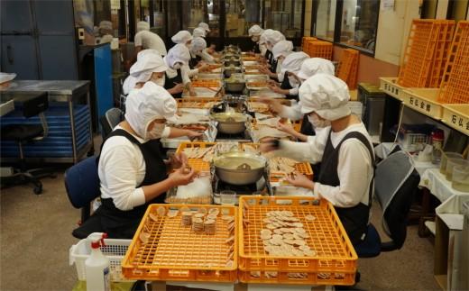 煎餅塗りの作業風景。一人で一日1千枚もの煎餅に生姜糖を塗ります。