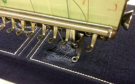 濃紺デニムに刺繍とレーザー加工で立体感ある柄を描いています