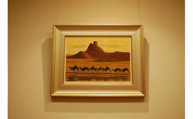 朝陽の中、中国の桜蘭を歩く駱駝の隊商を描いた絵画(木版画)。