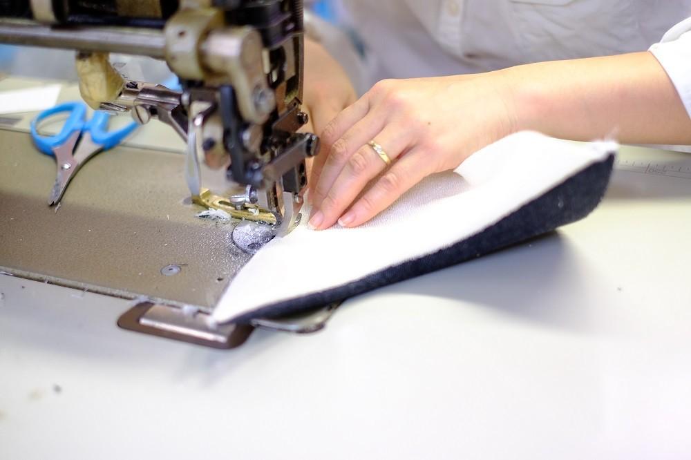 甲の縫い付け作業。手早さと正確さに、熟練の輝きがあります。