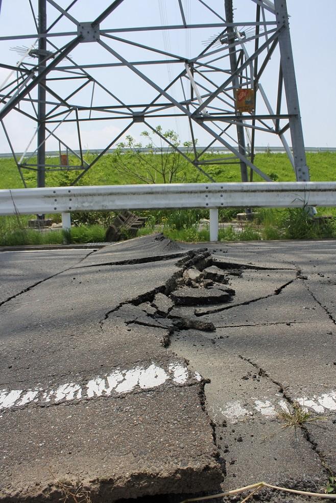 段差ができ、ひび割れた道路