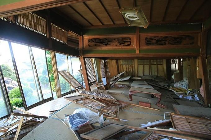 家屋が傾き、柱やふすまが折れ窓ガラスが割れた室内